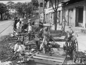 Hindu children picking through the burned ruins of rickshaws in the wake of the destruction caused by Musliml riots in this predominately Muslim area, on Wellesly St. in the city